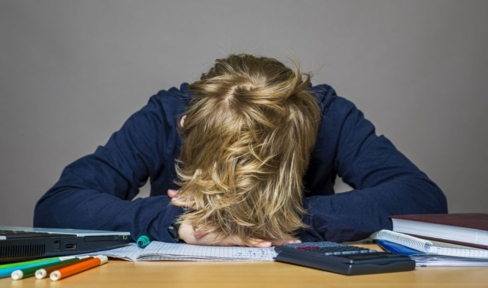 Jugendlicher hat Kopf auf Schreibtisch gelegt